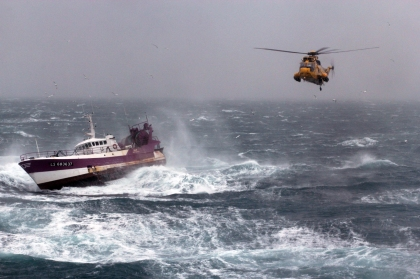 A Royal Air Force search and rescue Sea King helicopter comes to the aid of the French Fishing vessel Alf (LS683637) during a storm in the Irish Sea. The helicopter crew rushed to the aid of an injured fisherman trapped by bad weather on the Irish Sea. The Royal Navy Hydrographic survey vessel HMS Echo was carrying out maritime security operations when she received a request for assistance from Milford Haven Coastguard. The coastguard had already scrambled both an RAF search and rescue helicopter and an RNLI lifeboat to rescue the fisherman, but weather conditions were deteriorating fast. The 5 metre high swell meant it was not possible to lower a winchman safely onto the French vessel's deck and assist the fisherman who was showing signs of hypothermia. Once Echo was called in, the 3,500 tonne ship attempted to provide some shelter for the RNLI lifeboat to get alongside the French fishing vessel, Alf, but once again the weather prevented a rescue. This left them with no choice but to escort the fishing vessel closer inland before the helicopter was able to winch the injured fisherman to safety.