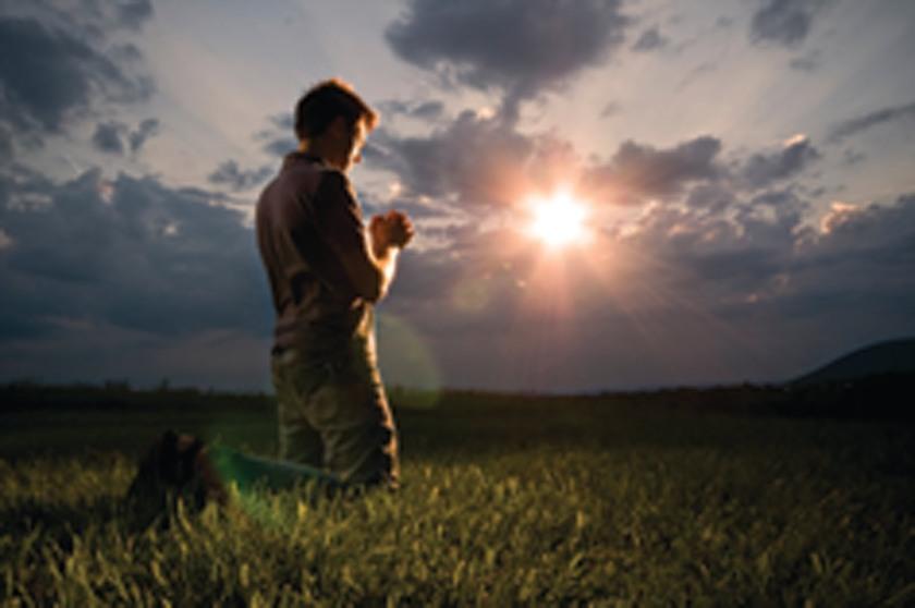 man kneeling praying sunset